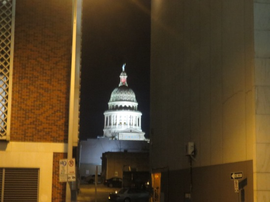 Capital building at night poking out from an alley